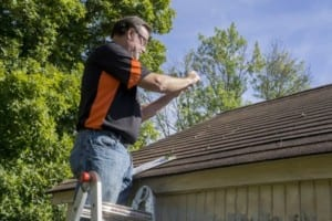 roofer taking photos of hail damaged roof